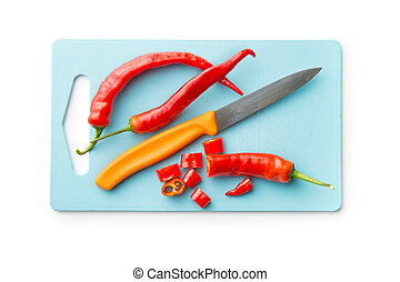 Sliced chili peppers and knife on cutting board.