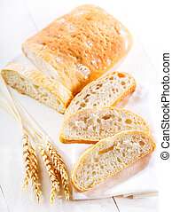sliced ciabatta bread with wheat ears on wooden table