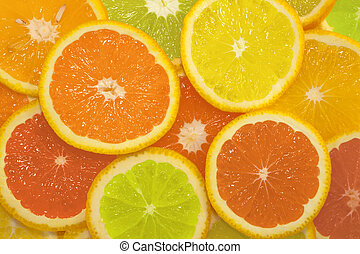 Sliced citrus fruits in different colors, background