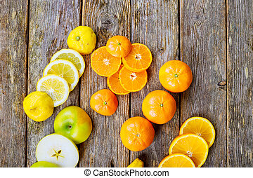 sliced citrus mix lemon grapefruit lime and orange in geometrical shapes on dark wood rustic background
