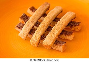 Sliced crispy bread in orange ceramic dish.
