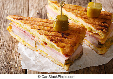 Sliced Cuban sandwich close-up on paper on a table. horizontal