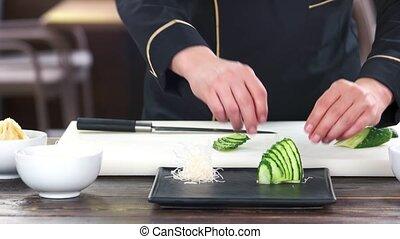 Sliced cucumber and kataifi dough. Male hands preparing...