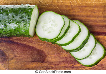 sliced cucumber on wooden cutting board