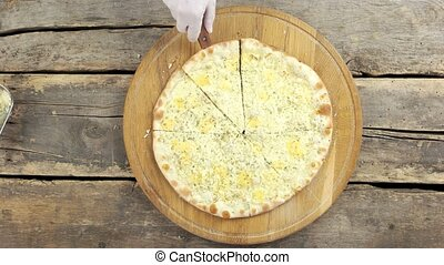 Sliced four cheese pizza. Tasty vegetarian food.
