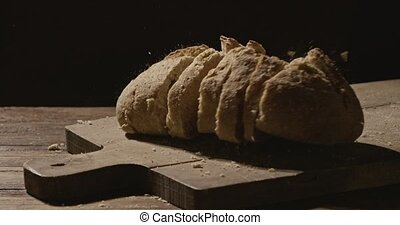 Sliced fresh bread falls on a wooden board on a dark ...