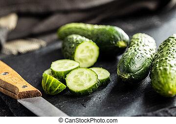 Sliced fresh green cucumbers on cutting board.