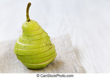 Sliced fresh pear on cloth, close-up. Side view. Copy space.