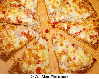 Sliced fresh pizza with red pepper on wooden board