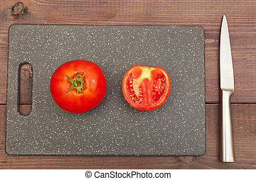 Sliced fresh tomato on cutting board on wooden table. View from above.