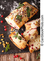 sliced fruit cake with cranberries and raisins decorated with mint close up. vertical