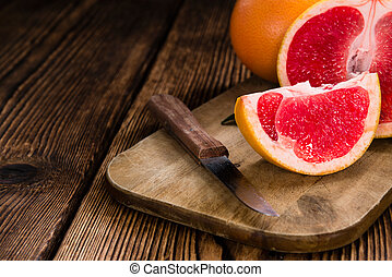 Sliced Grapefruit (close-up shot) on rustic wooden ...