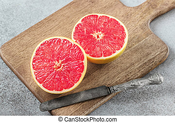 Sliced grapefruit on cutting board with knife