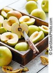Sliced green apples in a wooden box.