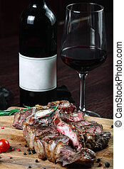 Sliced grilled T-bone steak tomatoes on a cutting board with bottle of wine and wineglass on dark background