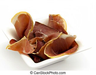 Sliced ham served on a rectangular plate, surrounded by...