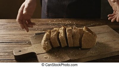 Sliced home bread a man throws on a wooden board - Pieces of...