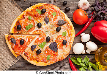 Sliced italian pizza margherita with tomatoes, olives and basil