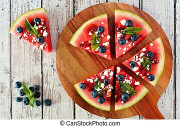 Sliced, juicy watermelon pizza with blueberries, feta cheese, mint and balsamic glaze, overhead view on serving board
