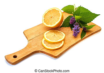 Sliced lemon and branch of flowering mint on wooden board over white background.