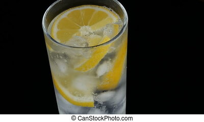 Sliced lemon in a long glass with ice cubes and cold soda on...