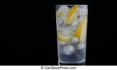 Sliced lemon in a long glass with ice cubes and cold soda on a black background. Refreshing Lemonade Bubbles.