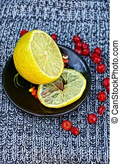 sliced lemon on a black plate with red berries on woolen cloth
