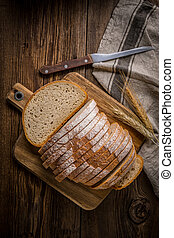 Sliced loaf of bread on a chopping board.