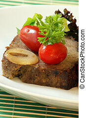 sliced meat loaf with organic parsley on a plate