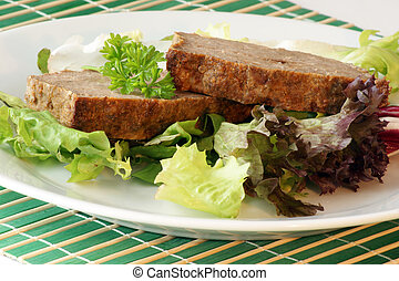 sliced meat loaf with organic vegetable on a plate