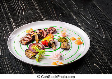 Sliced meat with fresh herbs, vegetables and spices on a white plate on a black wooden background, top view