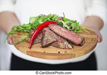 Sliced medium rare grilled Beef steak Ribeye in hands of a woman