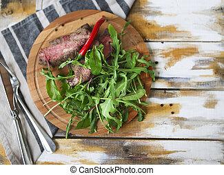Sliced medium rare grilled Beef steak Ribeye with rocket salad on cutting board
