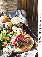 Sliced medium rare grilled Beef steak Ribeye on cutting board on wooden background