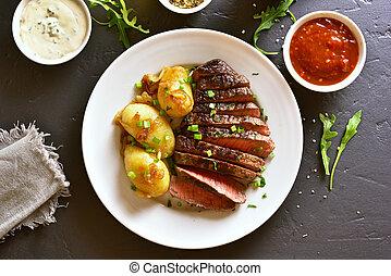 Sliced medium rare roast beef with potato