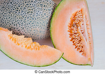 Sliced melon with seed on wooden board