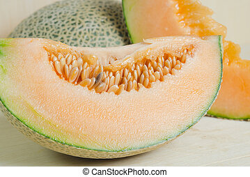 Sliced melon with seed on wooden board (Other names are Melon, cantelope, cantaloup, honeydew, Crenshaw, casaba, Persian melon, and Santa Claus or Christmas melon)