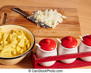 Sliced onions on table. Potatoes.
