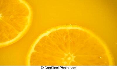 Sliced orange falling into orange juice