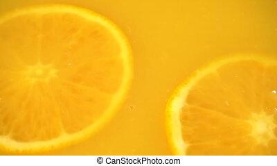 Sliced orange falling into orange juice in slow motion