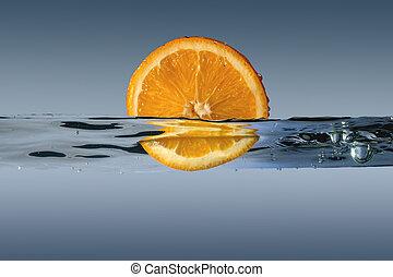 sliced orange in water on a blue background