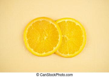 Sliced orange on yellow background