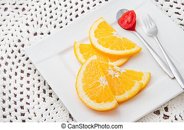 sliced oranges on white plate with red tomato on the spoon