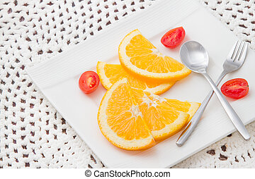 sliced oranges on white plate with red tomato