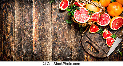 Sliced pieces of grapefruit with a knife.