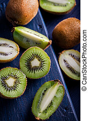 Sliced pieces of kiwi on a wooden background