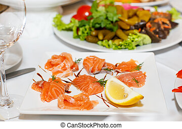 Sliced pieces of salmon and lemon on a white plate