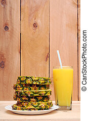 sliced pineapple and juice on wooden table