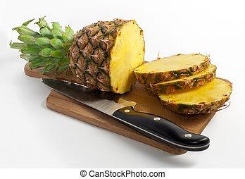 sliced pineapple on wooden desk with knife, on white