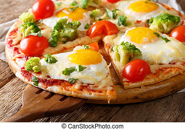 Sliced pizza with eggs, broccoli, tomatoes and parsley close-up. horizontal